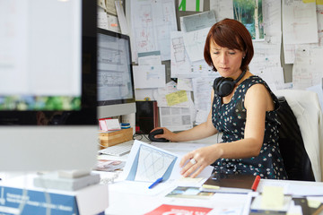 Female designer at office desk looking at blueprint