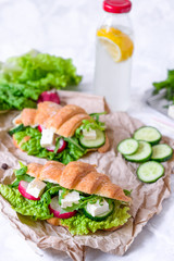 Croissant sandwich with cheese and vegetables for healthy snack, craft paper and greens background. Picnic summer food. Selective soft focus