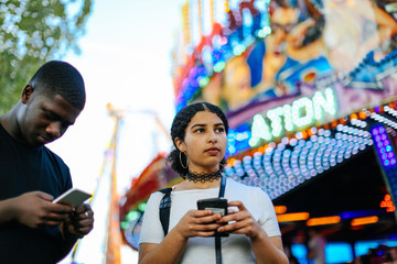Two friends at funfair, holding smartphones
