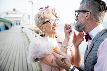 1950's vintage style mature woman wiping boyfriend's beard on pier