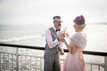 1950's vintage style couple sharing ice cream cone on pier