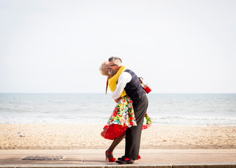 1950's vintage style couple hugging each other at beach