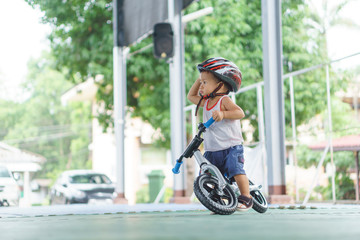Asian boy is playing with baby balance bike