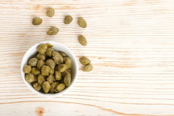 capers on wooden background