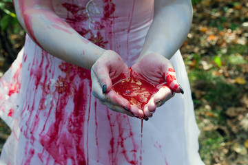 Hands of a girl in white dressed together full of red blood