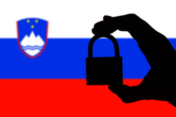 Slovenia security. Silhouette of hand holding a padlock over national flag