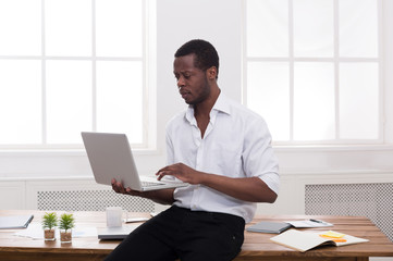 Black businessman in casual office, work with laptop