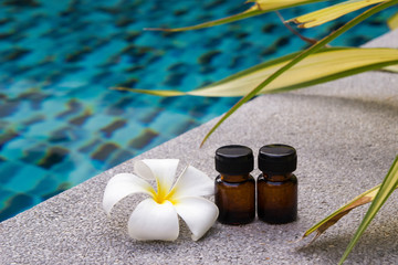 Bottles of aroma essential oil and flower of frangipani (or plumeria) on the swimming pool background for spa theme.