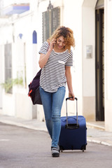Full length happy young female traveler walking with suitcase and cellphone