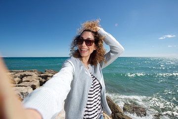 happy young woman smiling and taking selfie by the sea
