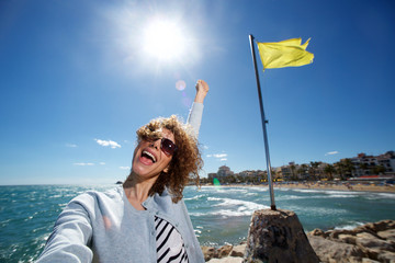 young woman smiling with arm in air while taking selfie at the beach