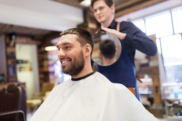 man and hairdresser with mirror at barbershop