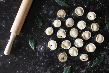 Preparation of pelmeni. Top view. Ingredients on black table. Traditional Russian cuisine.