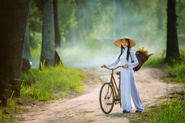 beautiful woman with Vietnam culture traditional dress, Ao dai and riding bicycle