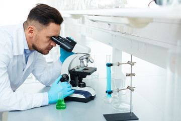 Portrait of handsome scientist using microscope in laboratory while working on important medical research inventing drugs