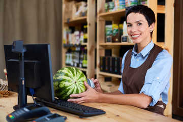 Pretty cashier with stylish haircut posing for photography while scanning barcode of watermelon in organic food store, waist-up portrait