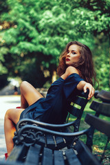 Attractive young woman posing on a bench in the park