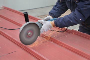 Worker using angle grinder to cut roof or wall panel at construction site