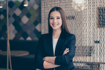 Successful and confident business lady lawyer standing with crossed hands at her work place in coworking modern office, looks in the camera, She is in a black jacket, smiling