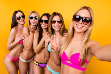 Cheers! Selfie mania! Joy time! Five young cute ladies in sunglasses are posing for a selfie photo shot, blond is taking. They are all in fashionable, trendy swim wear, gesturing, making memories