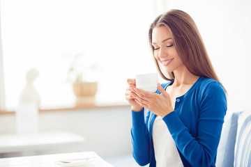 Good morning! Close up portrait of charming dreamy brunette young girl drinking coffee. She is sleepy and relaxed, in casual blue wear, in light room