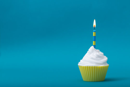 yellow birthday cupcake with candle against blue background