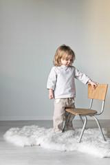 kleines Kind spielt zuhause mit einem Stuhl