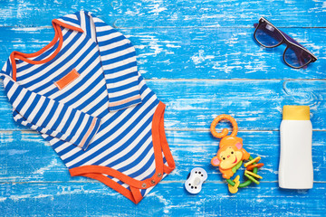 Foto op Plexiglas Draw Baby Child summer stuff to the beach on a blue wooden background. Top view with copy space for text.