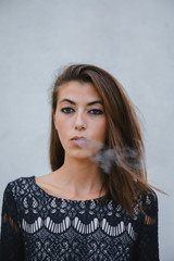 Woman puffing smoke looking at camera