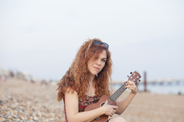 Young woman playing ukulele in a stone beach