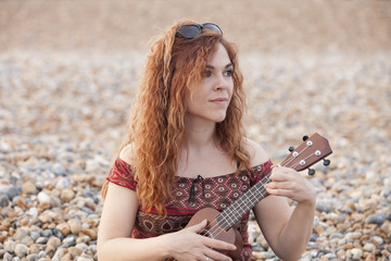 Red hair woman playing ukulele in a beach