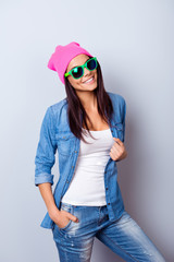 Portrait of a playful young funky mulatto girl in a stylish casual clothes and bright green sunglasses, pink hat, standing on the blue background