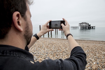 Man taking a photo in the sea with a smart phone