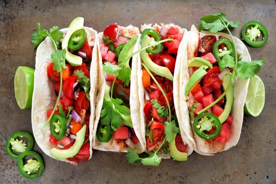Spicy fish tacos with watermelon salsa and avocados, above view on rustic metallic background