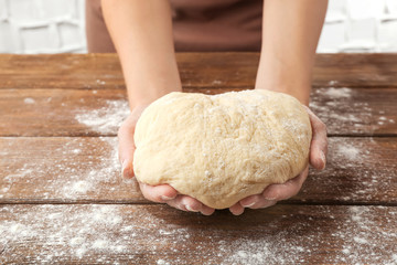 Woman holding dough for pizza