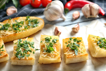 Tasty bread slices with grated cheese, garlic and herbs on parchment