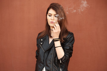 Beautiful young woman smoking weed outdoors on color background