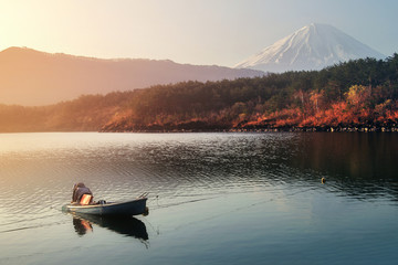 Fishermen are fishing at Lake Saiko with beautiful scenery of nature during sunrise and the beautiful of Mountain Fuji in Japan. Activities and travel concept