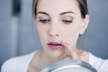 Woman applying cream to treat labial herpes