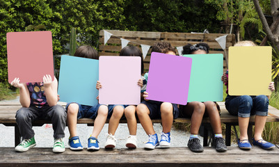 Group of children holding blank banner cover their face Wall mural