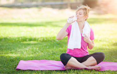 Young Fit Adult Woman Outdoors On Her Yoga Mat with Towel Drinking From Her Water Bottle.