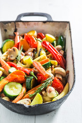 Roasted vegetables in casserole on white background