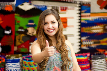 Beautiful smiling young woman with humbs up and posing for camera, with colorful andean traditional clothing fabrics background