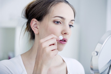 Woman applying a patch to treat labial herpes
