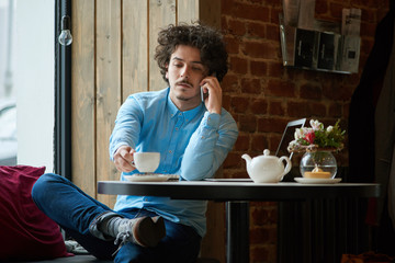 Cute young man talking by the phone and holding a cup of coffee