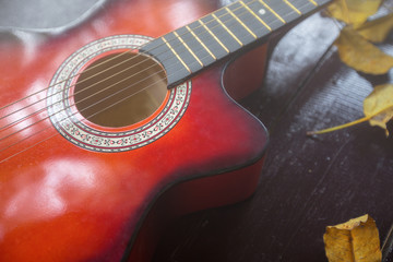 Red acoustic guitar at the wooden floor