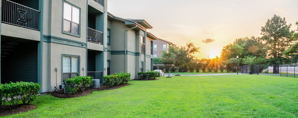 View from grassy backyard of a typical apartment complex building in suburban area at Humble, Texas, US. Sunset with warm light. Panorama style.