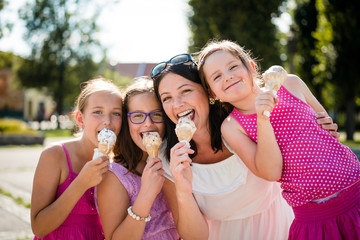 Mother with three daughters eating ice cream. Fun day outdoor.