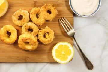 Calamari rings, mayonnaise sauce, lemon, copy space