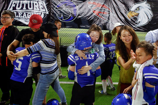 Players of the Eagles celebrate after their team defeated the Sharklets in their Future League American football youth league match in Beijing